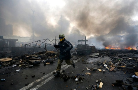 An anti-government protester runs trough the rubble after violence erupted in the Independence Square in Kiev